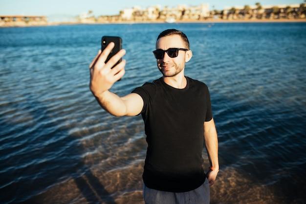 Jovem feliz de férias rindo na praia tirando selfie com óculos de sol no mar