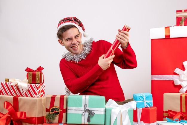 Jovem feliz de frente, usando o popper de festa sentado em volta dos presentes de natal