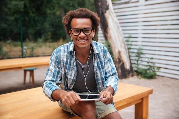 Jovem feliz de óculos e fones de ouvido usando tablet no parque