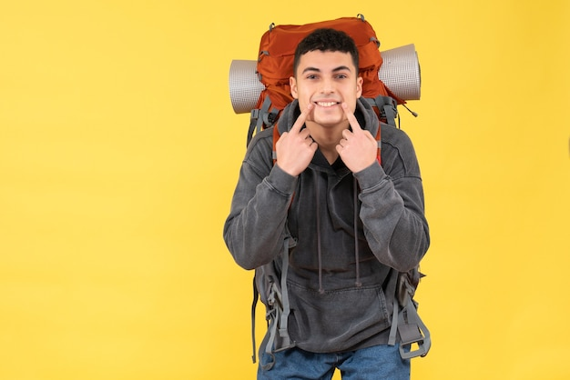 Jovem feliz de vista frontal com mochila vermelha apontando para o sorriso