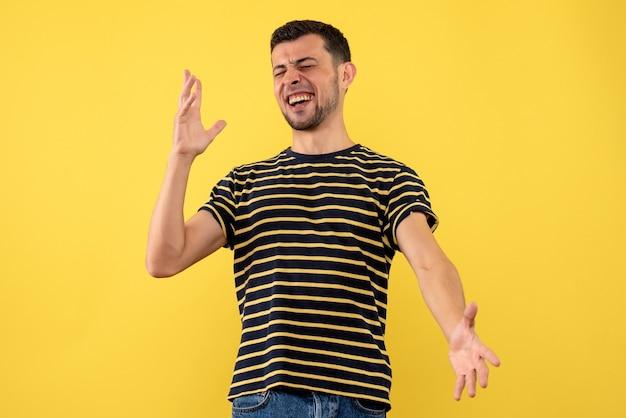 Jovem feliz de vista frontal em uma camiseta listrada de preto e branco amarelo isolado de fundo