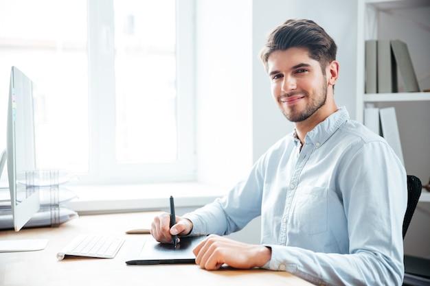 Jovem feliz designer sentado e usando a mesa digitalizadora no local de trabalho