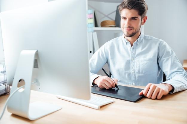 Jovem feliz designer trabalhando usando computador e tablet gráfico no local de trabalho