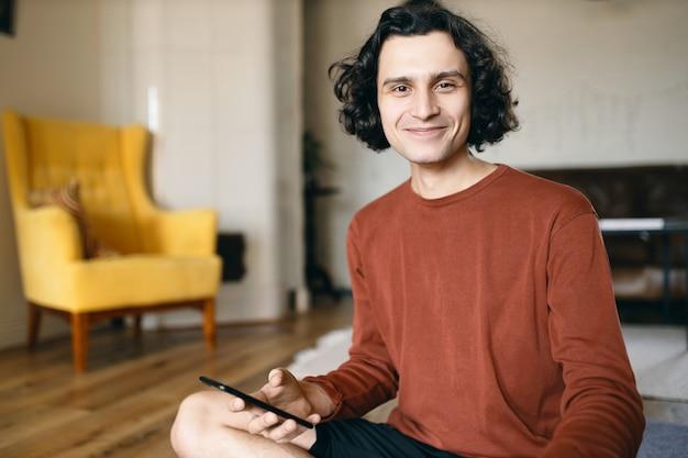 Jovem feliz do sexo masculino com cabelo preto ondulado, aproveitando a comunicação online usando uma conexão de internet sem fio de alta velocidade no telefone inteligente