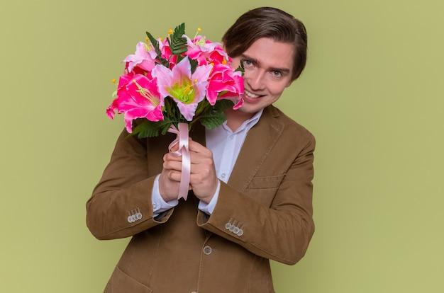 Jovem feliz e alegre segurando um buquê de flores, olhando para a câmera
