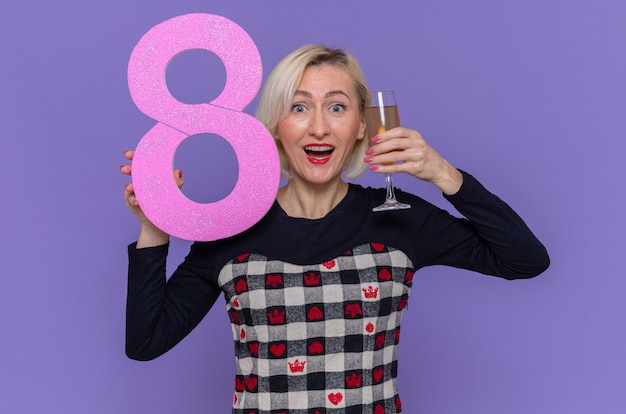 Jovem feliz e animada segurando o número oito feito de papelão e uma taça de champanhe