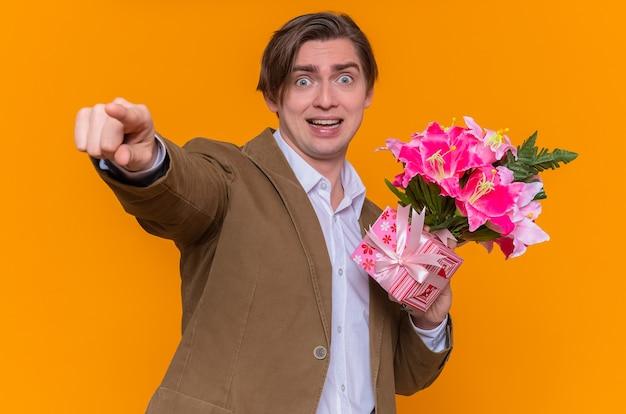 Jovem feliz e animado segurando um buquê de flores apontando