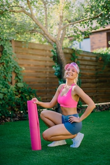 Jovem feliz e atlética sentada na grama com um tapete de ioga