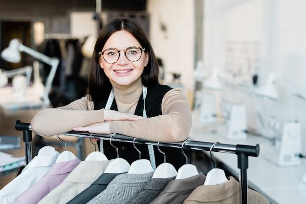 Jovem feliz e bem-sucedida estilista feminina ou assistente de loja olhando para você ao lado da raquete com novos casacos