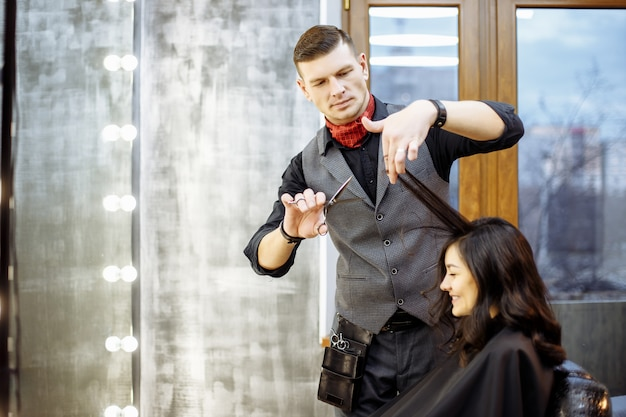 Jovem feliz e cabeleireiro cortar as pontas do cabelo no salão.