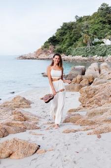 Jovem feliz e calma mulher caucasiana com ukulele na praia tropical rochosa ao pôr do sol