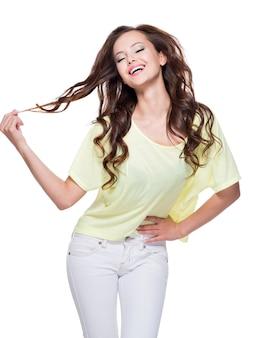 Jovem feliz e expressiva com longos cabelos castanhos cacheados posando
