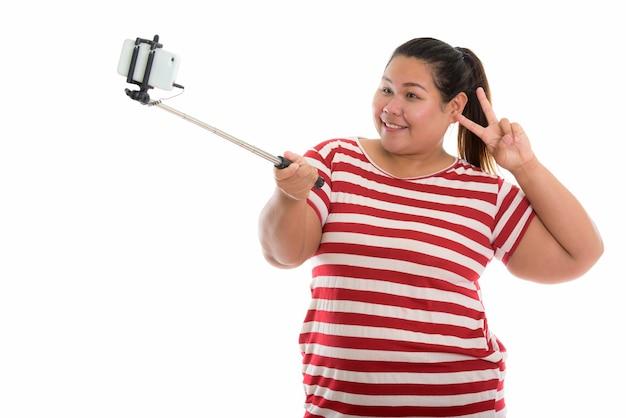 Jovem feliz e gorda asiática sorrindo e tirando uma selfie