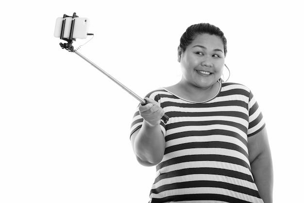 Jovem feliz e gorda asiática sorrindo enquanto tira uma foto de selfie com o celular no stick de selfie
