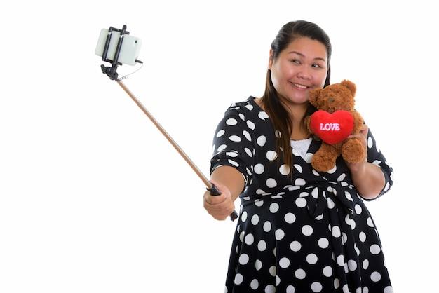 Jovem feliz e gorda asiática sorrindo enquanto tira uma selfie
