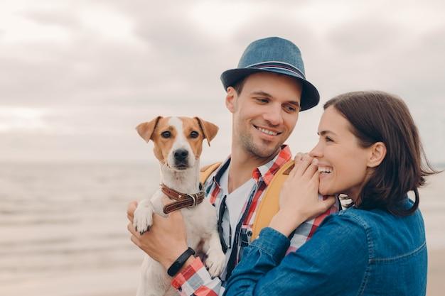 Jovem feliz e homem vestido com chapéu e camisa, levar cão de raça, se divertir juntos