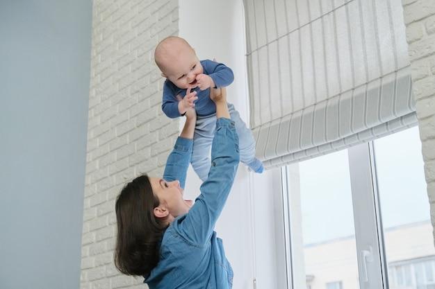 Jovem feliz e linda mãe brincando com o filho pequeno