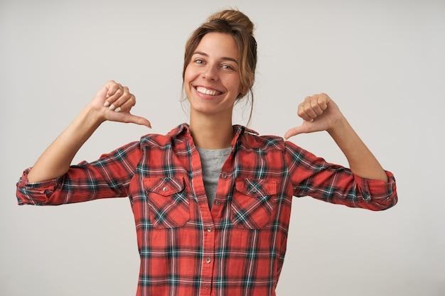 Jovem feliz e linda mulher com penteado coque, vestindo camisa xadrez e camiseta, posando em branco com as mãos levantadas, apontando com os polegares para si mesma e sorrindo amplamente