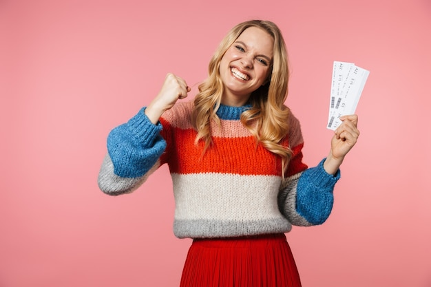 Jovem feliz e linda mulher posando isolada na parede rosa segurando ingressos