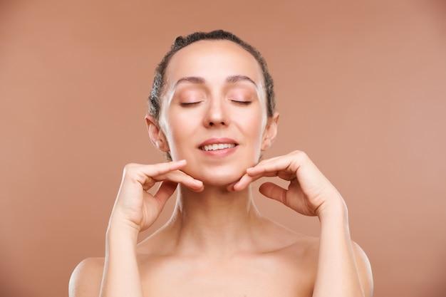 Jovem feliz e linda mulher tocando seu queixo durante uma massagem facial e procedimento de beleza para cuidados com a pele