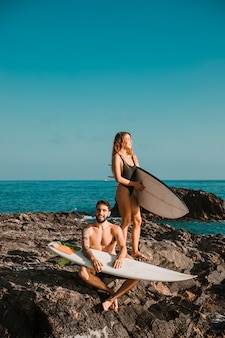 Jovem feliz e mulher com pranchas de surf na rocha perto do mar