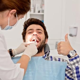 Jovem feliz e mulher em um exame dentário no dentista