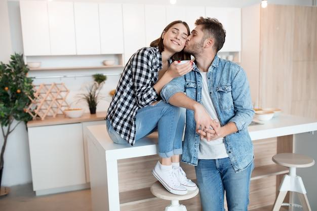 Jovem feliz e mulher na cozinha, café da manhã, casal juntos pela manhã, sorrindo, tomando chá