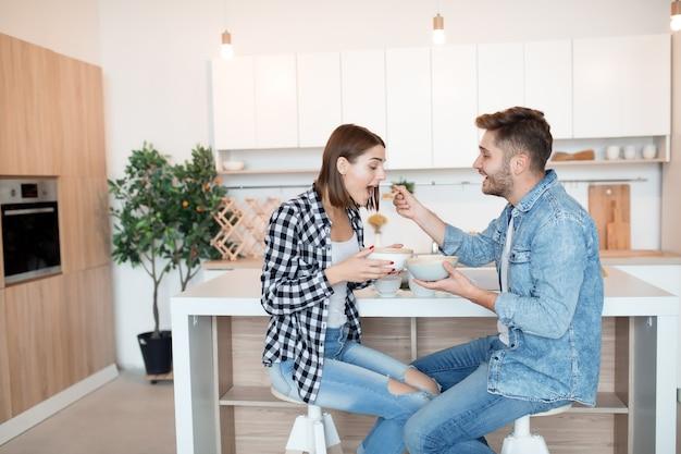 Jovem feliz e mulher na cozinha, tomando café da manhã, casal juntos pela manhã, sorrindo