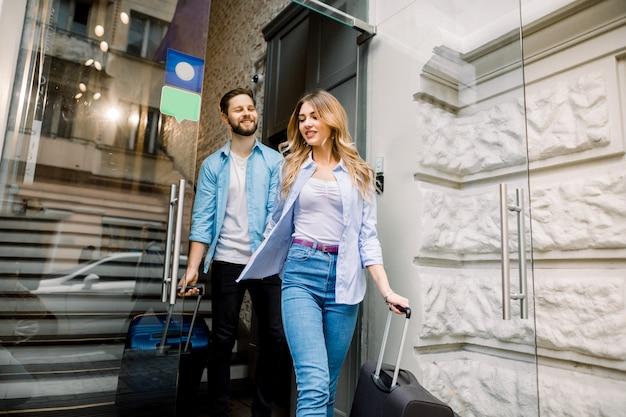Jovem feliz e mulher saindo do hotel com bagagem