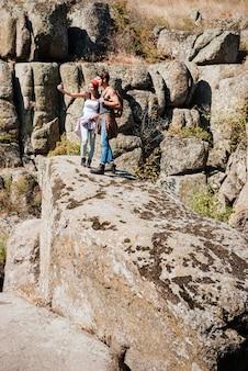 Jovem feliz e mulher tirando um auto-retrato com uma paisagem de montanhas ao fundo