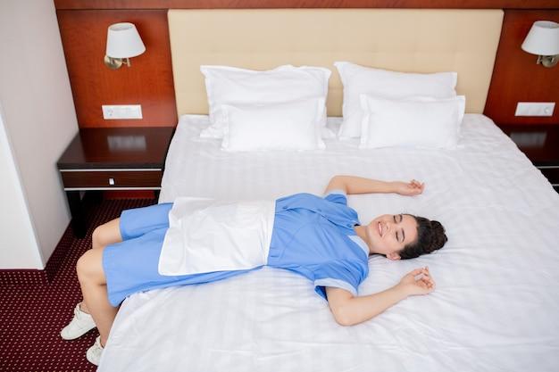 Jovem feliz e relaxada camareira de uniforme deitada em uma cama branca e limpa enquanto faz uma pausa no dia de trabalho