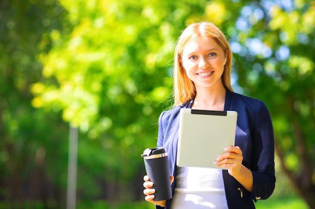 Jovem feliz e sorridente caucasiana sucesso adulto caminhando no parque com tablet e telefone