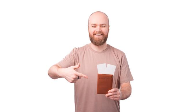 Jovem feliz e sorridente com barba apontando para passaporte e passagens