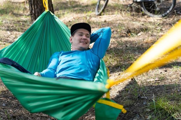 Jovem feliz e sorridente com chapéu relaxando do lado de fora em uma rede na floresta