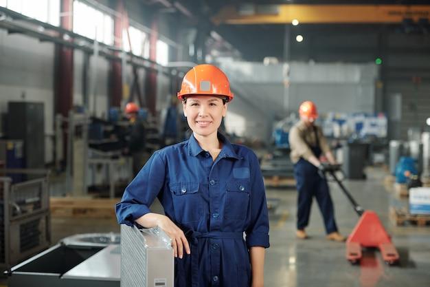 Jovem feliz e sorridente engenheira com capacete e macacão azul, olhando para você enquanto está no depósito da fábrica
