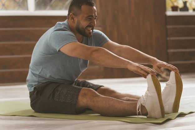 Jovem feliz e sorridente homem fitness fazendo exercícios de alongamento em casa