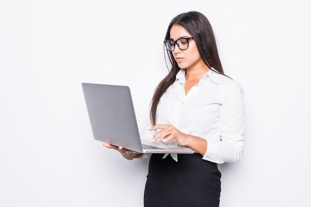 Jovem feliz e sorridente mulher de negócios em roupas casuais segurando um laptop e enviando e-mail isolado no branco