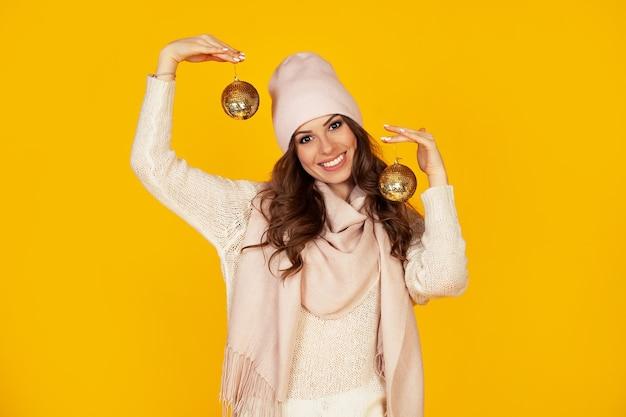 Jovem feliz e sorridente segurando bolas de natal