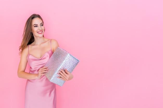 Jovem feliz e sorridente segurando uma caixa de presente no conceito de celebração do fundo rosa isolado do estúdio