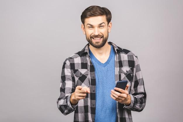 Jovem feliz em casual digitando sms na parede cinza, sorrindo e olhando