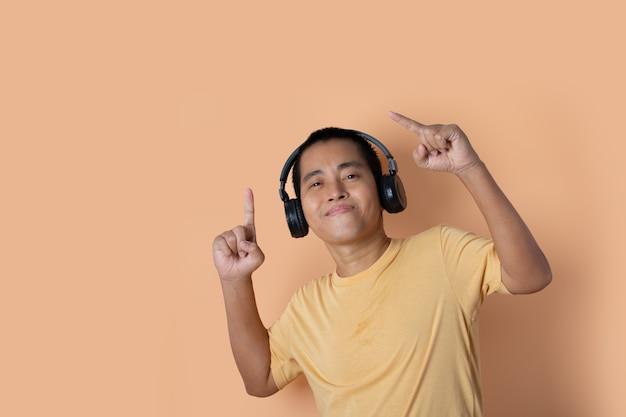Jovem feliz em fones de ouvido, ouvindo música e dançando em fundo laranja do estúdio. ouvindo música.