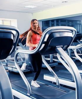 Jovem feliz em forma de mulher correndo na esteira na academia moderna e bem iluminada