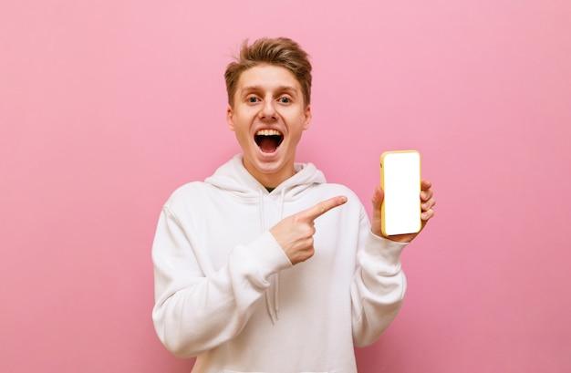 Jovem feliz em pé no fundo rosa com smartphone na mão em fundo rosa, olhando para a câmera com cara de surpresa e mostrando o dedo na tela preta.