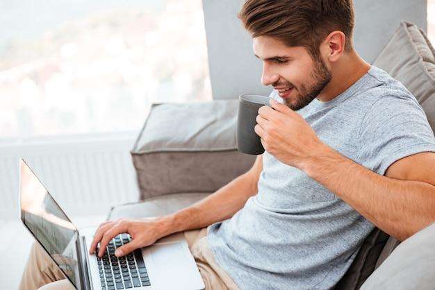 Jovem feliz em t-shirt cinza, sentado no sofá em casa. trabalhando no laptop e sorrindo enquanto bebia um café.