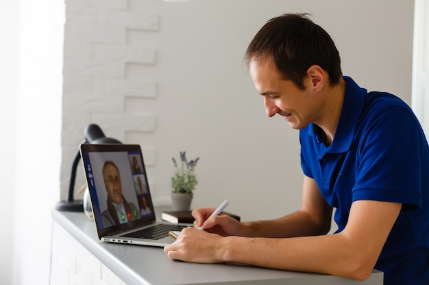 Jovem feliz em t-shirt sentado em casa, trabalhando no computador portátil, sorrindo.