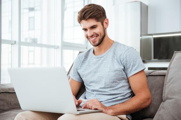 Jovem feliz em t-shirt sentado no sofá em casa. trabalhando no laptop e sorrindo.