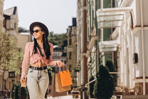 Jovem feliz em um dia ensolarado na rua com sacolas de compras. banner do site