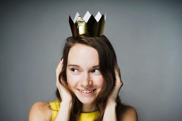 Jovem feliz em um vestido amarelo fechou as orelhas, sorrindo, na cabeça uma coroa de ouro