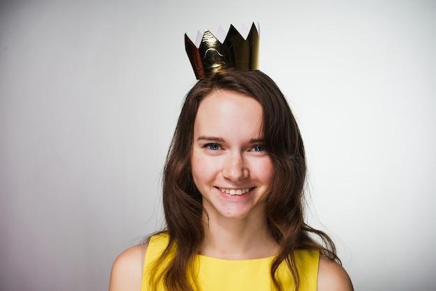 Jovem feliz em um vestido amarelo sorrindo, na cabeça uma coroa de ouro