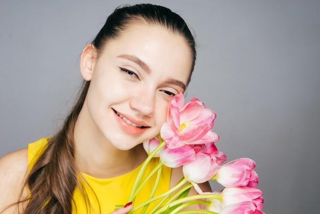 Jovem feliz em um vestido amarelo sorrindo, segurando um buquê de flores rosa perfumadas e sorrisos